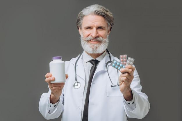 De gebaarde senor arts houdt pillen op grijze muur stand