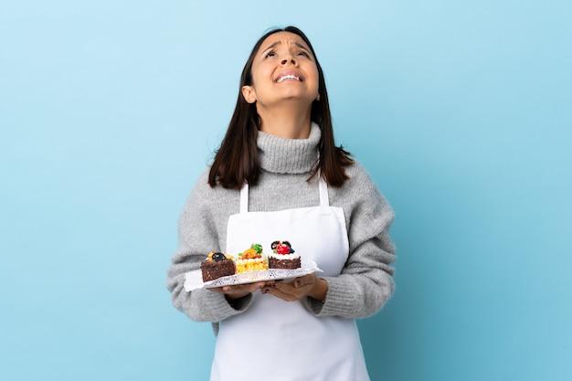 De gebakjechef-kok die een grote cake over geïsoleerde blauwe muur houden houdt palm samen. persoon vraagt iets