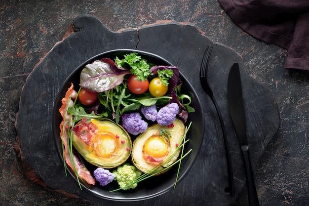 De gebakken avocado met vlak ei en bacon, legt op donkere achtergrond