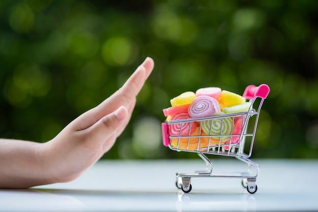 De gebaren van een vrouwenhand om full colour snoep af te wijzen dat wordt in de kar gelegd