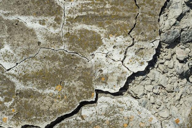De gebarsten concrete achtergrond van de de close-uptextuur van de cementtextuur
