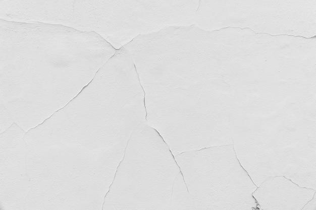 De gebarsten witte achtergrond van de muurtextuur
