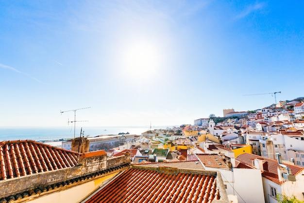 De gebouwen op een heuvel en een prachtig uitzicht op zee in lissabon