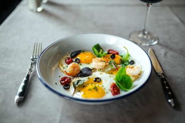 De gebraden eieren van de close-uppompoen ontbijt met garnalen