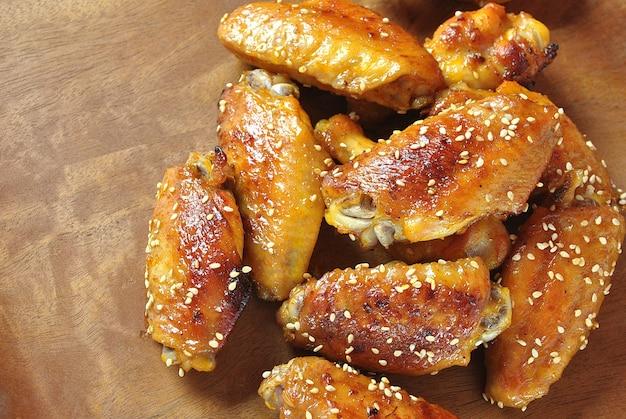 De gebraden vleugels van de barbecuekip sluiten omhoog op houten dienbladschot met selectieve nadruk
