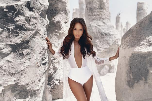 De gebruinde sexy jonge vrouw met make-up en donker haar, gekleed in zomer witte kleding die zich voordeed in de buurt van witte rotsen
