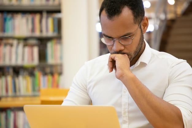 De geconcentreerde hand van de jonge mensenholding op kin en het bekijken laptop