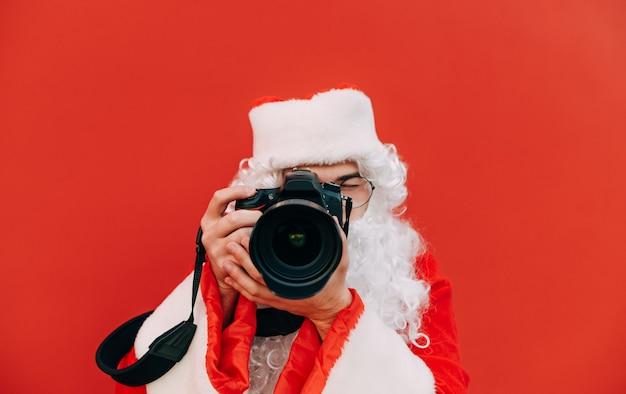 De geconcentreerde kerstman neemt foto's op de camera