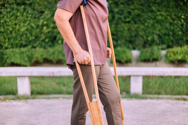 De geduldige bejaarde aziatische vrouw die steunpilaren gebruiken steunt gebroken benen voor het lopen bij openbaar park, fysiotherapieconcept