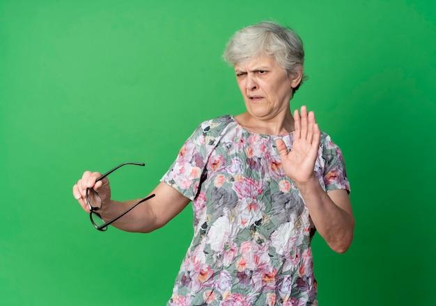 De geërgerde bejaarde houdt optische glazen die hand opheffen die op groene muur wordt geïsoleerd