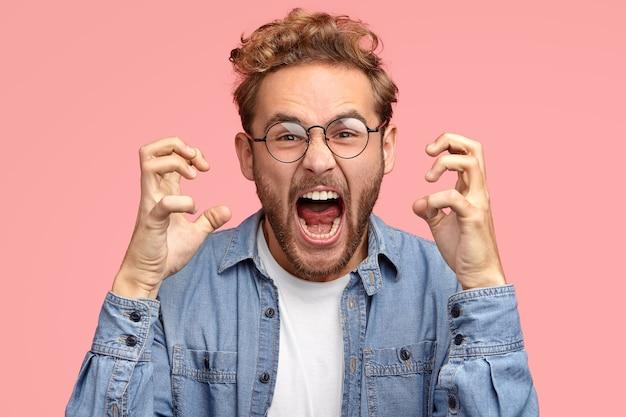 De geërgerde man van peevish gebaart boos, drukt negatieve emoties uit, houdt de mond wijd open