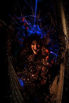 De geestvrouw, de geest van het theater, gromt de gordijnen terug