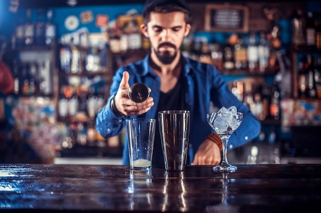 De gefocuste barman formuleert een cocktail terwijl hij naast de bar in de pub staat