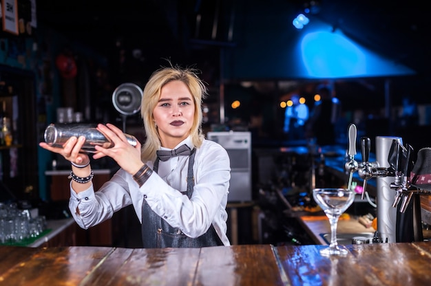 De gefocuste barmeisje demonstreert het proces van het maken van een cocktail terwijl ze naast de toog in de bar staat