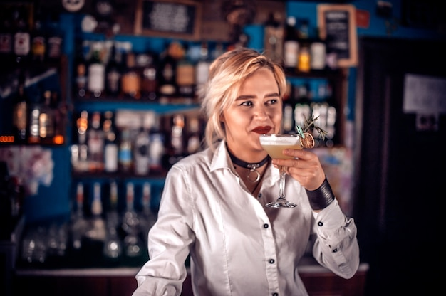 De gefocuste meisjesmixoloog demonstreert zijn professionele vaardigheden in de pub