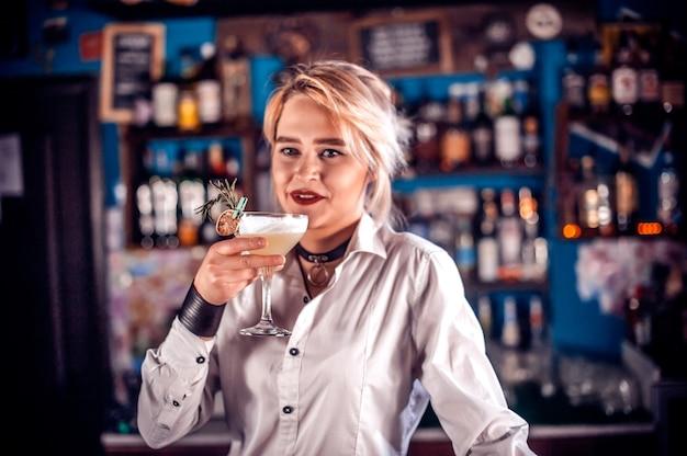 De gefocuste meisjesmixoloog demonstreert zijn vaardigheden over de toonbank aan de bar