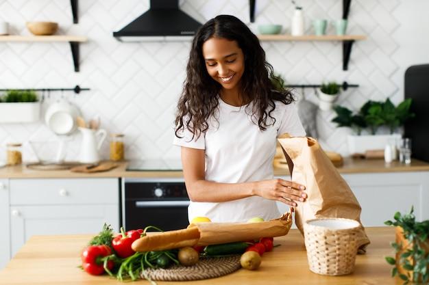 De geglimlachte mooie mulatvrouw zet pakketten met voedsel op de lijst op de moderne keuken