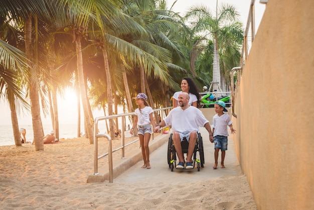 De gehandicapte mens in een rolstoel beweegt zich met een gezin op een helling naar het strand.