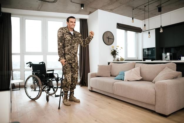 De gehandicapte mens leunt op kruk dichtbij rolstoel in ruimte.