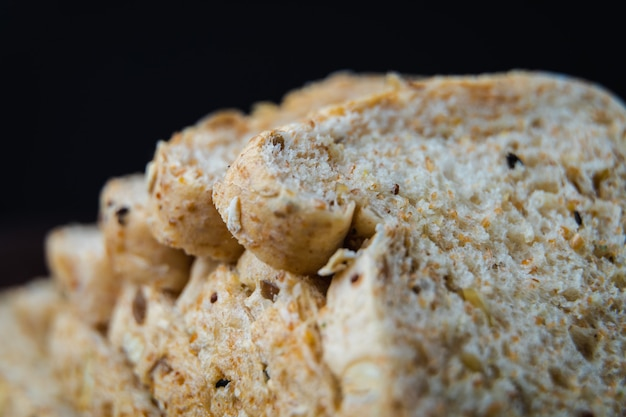De gehele tarwe, het gehele korrelsbrood op donkere rustieke houten raad, sluit omhoog