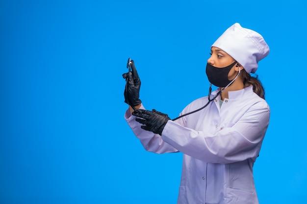 De geïsoleerde verpleegster controleert de patiënt met in hand stethoscoop en gezichtsmasker.