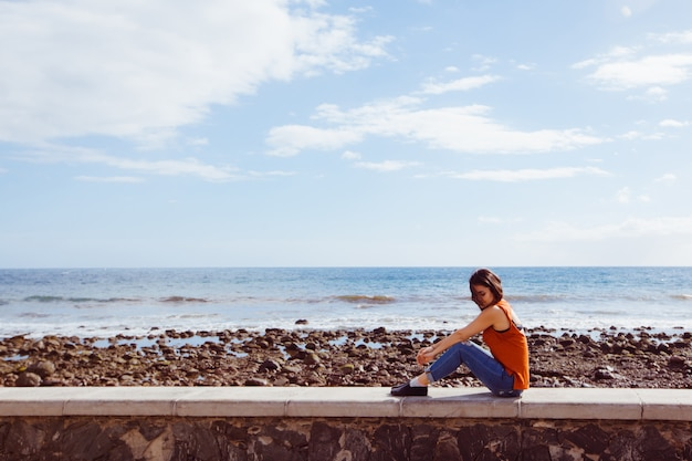 De geïsoleerde vrouw zit op het strand op vakantie. reis- en vakantie concept.