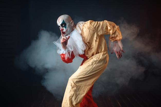 De gekke bloedige clown sluipt en toont het stille teken