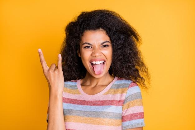 De gekke donkere huidmeisje steekt tong uit toont rock and roll-symbool