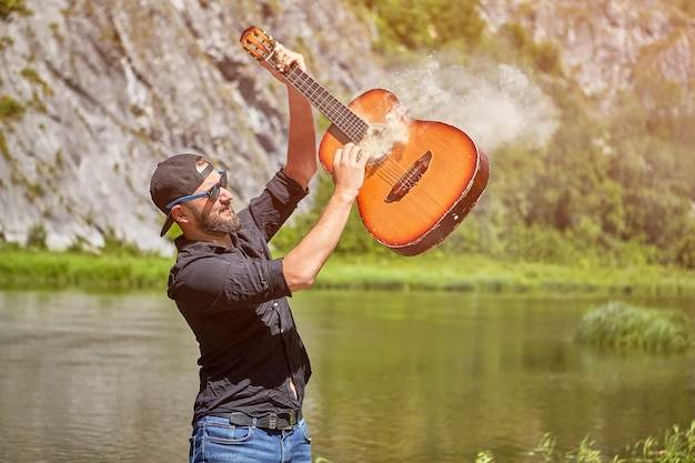 De gekke gitarist speelt rokende gitaar dichtbij bosrivier