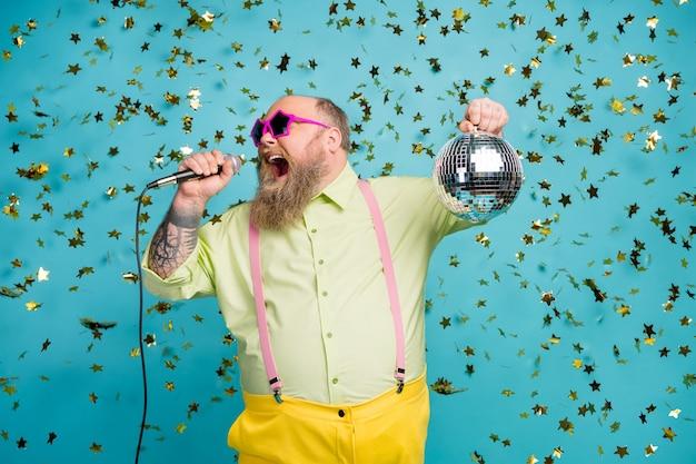 De gekke kerel houdt de discobal zingt karaoke op blauwe achtergrond met dalende confettien