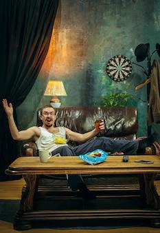 De gekke voetbalfan kijkt naar voetbalwedstrijd op televisie op de bankbank thuis met bier en ziet er angstig en bang uit om te verliezen. het nerveuze, opgewonden, lijden, stress, emoties concept