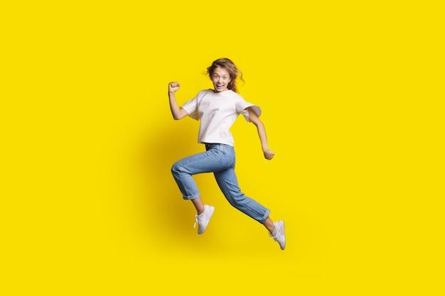 De gekke vrouw springt in een gele studiomuur die bij camera glimlacht die een run gebaart