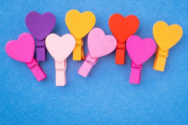 De gekleurde houten harten liggen zij aan zij op een blauwe achtergrond.