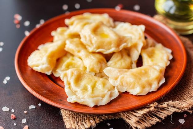 De gekookte gemaakte dumplings met een vulling met olie en groene uien op een donkere tafel. het kan als achtergrond worden gebruikt