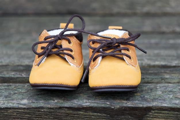 De gele babylaarzen sluiten omhoog. kid schoenen op houten bankje in het park.