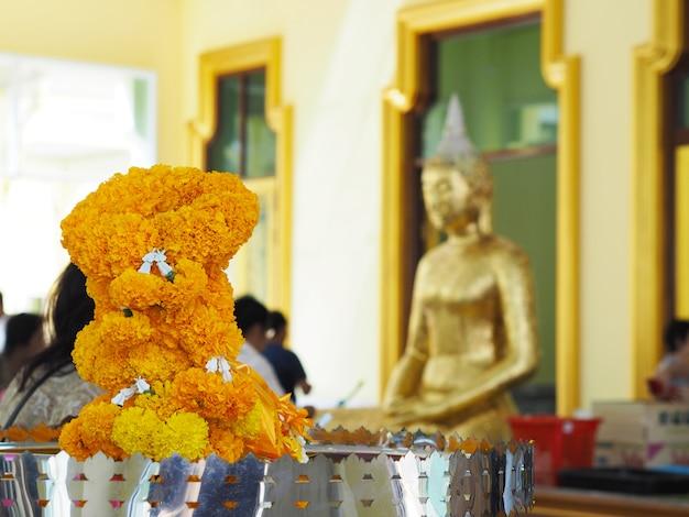 De gele bloemen van de goudsbloemslinger over onduidelijk beeldachtergrond van boeddhismemensen bij tempel in thailand.