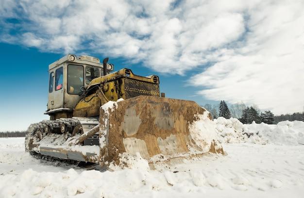 De gele bulldozer van de rupstrekker met een emmer werkt in de winter die de weg van sneeuw vrijmaakt.