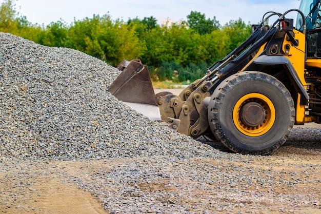 De gele bulldozer van de wiellader werkt in steengroeve