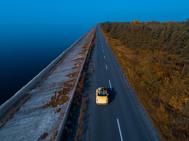 De gele cabriolet rijden op de kustweg