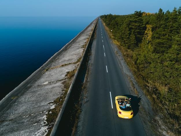 De gele cabriolet rijdt op de kustweg