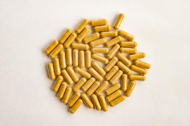 De gele capsules van kleurenpillen op witte achtergrond