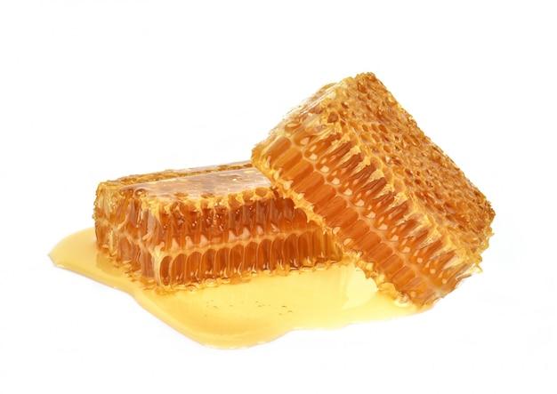 De gele close-up van de honingraatplak die op witte achtergrond wordt geïsoleerd