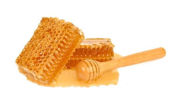De gele die close-up van de honingraatplak op witte achtergrond wordt geïsoleerd