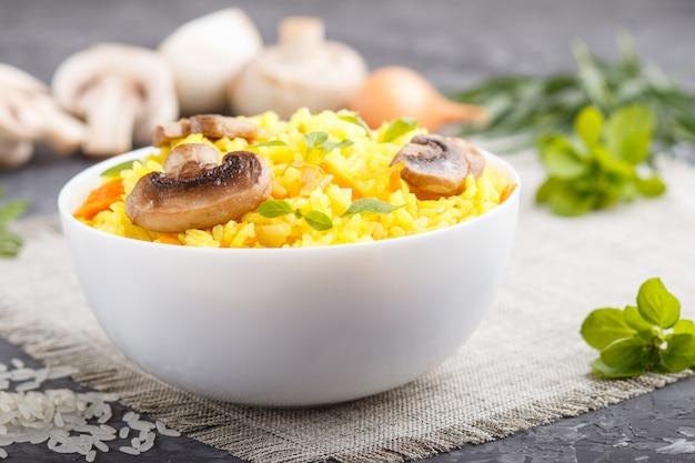De gele gebraden rijst met champignons schiet kurkuma en orego in witte ceramische kom op een zwarte concrete achtergrond als paddestoelen uit de grond