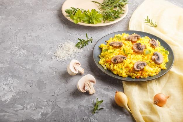 De gele gebraden rijst met champignons schiet kurkuma en orego op blauwe ceramische plaat op een grijze concrete achtergrond als paddestoelen uit de grond