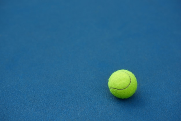 De gele heldere tennisbal ligt op blauwe tapijtachtergrond. gemaakt om te tennissen. blauwe tennisbaan.
