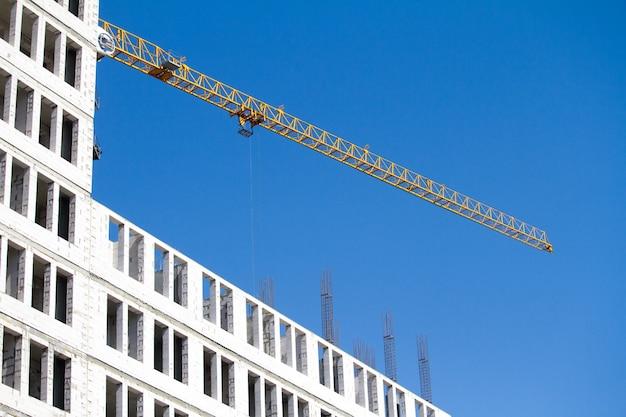 De gele kraan van de bouwtoren dichtbij nieuwbouw over blauwe hemel, selectieve nadruk