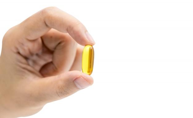 De gele pillen van de vistraancapsule in aziatische geïsoleerde vrouwenhand