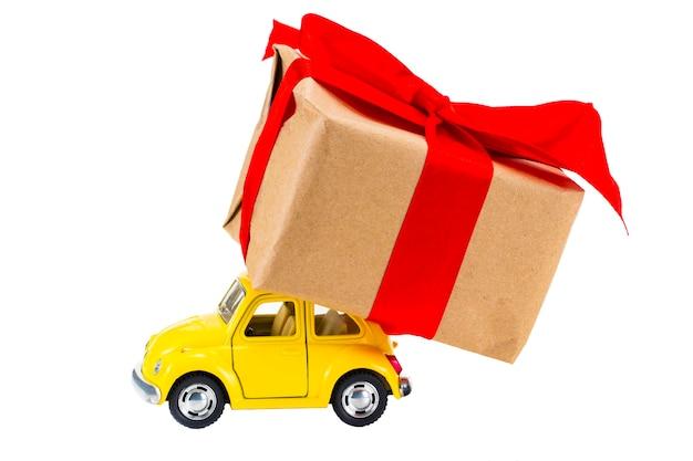 De gele retro speelgoedauto die de doos van geschenken levert op een witte achtergrond.