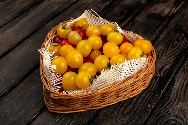 De gele rode tomaten verse rijpe vitamine riched binnen bruine kist op het rustieke houten bureau